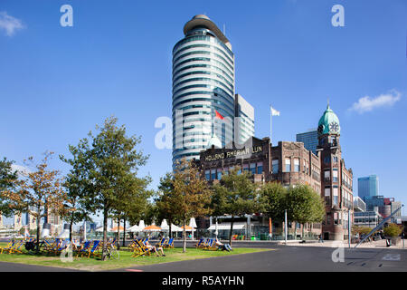 Rotterdam, Netherlands – September 18, 2018: Sunbathing in a beach chair in front of the famous Hotel New York on the south bank in Rotterdam - Stock Photo
