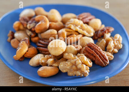 Close-up of a salted nuts mix on a blue dish - Stock Photo