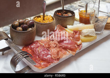 Portuguese tapas - smoked ham, salami, chorizo sausages, a variety of cheese, crackers, liver pate and several traditional jams - Stock Photo