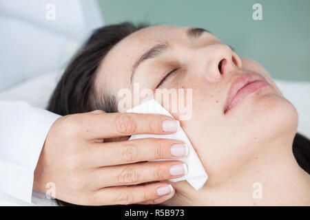 Doctor cleaning a woman patient face - Stock Photo