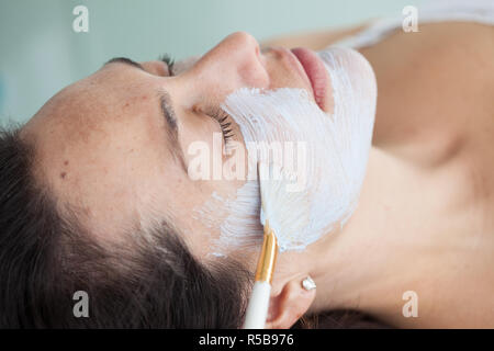 Facial mask application on woman face using a brush - Stock Photo