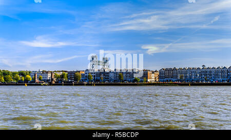 The Nieuwe Maas river with the historic houses on the shore of Noorder eiland in the center of the harbor city of Rotterdam in the Netherlands - Stock Photo