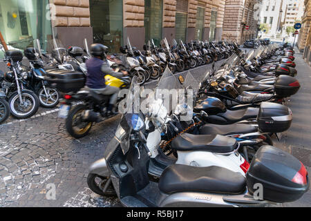 Rows of scooters and motorbikes, the most popular transport in Naples, parked in a street in the city centre,  Naples, Italy. - Stock Photo