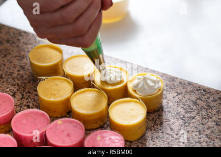Woman hand decorating mini cakes - Stock Photo