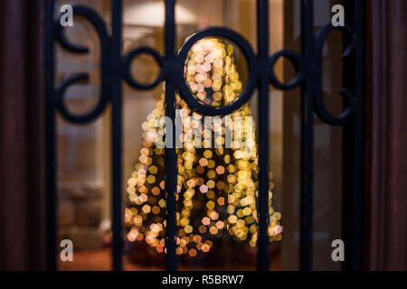 Abstract holidays blurry backdrop. Blurred background with glowing Christmas tree behind bars of window - Stock Photo