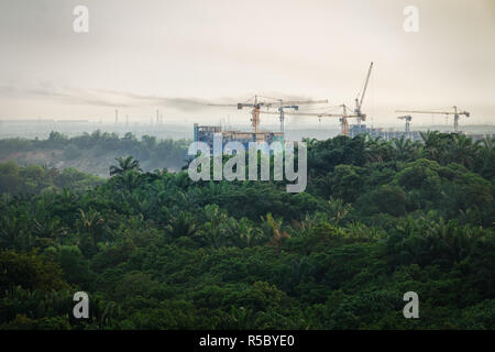 Tropical forest destruction - construction of skyscrapers in forest zone. Concept expansion of cities, increasing carbon dioxide in atmosphere. - Stock Photo