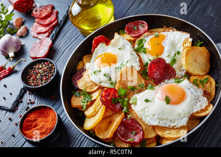 close-up of Traditional spanish huevos rotos - fried eggs with potatoes, pork sausages chorizo in a skillet on a black wooden table with ingredients,  - Stock Photo