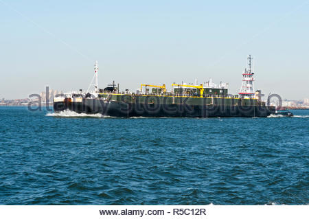 New York City, USA - February 1, 2009: Tug pushing barge across New York harbor - Stock Photo