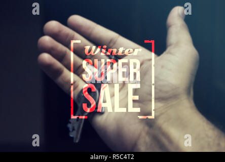 Real Estate Agent holding keys for winter sale. - Stock Photo