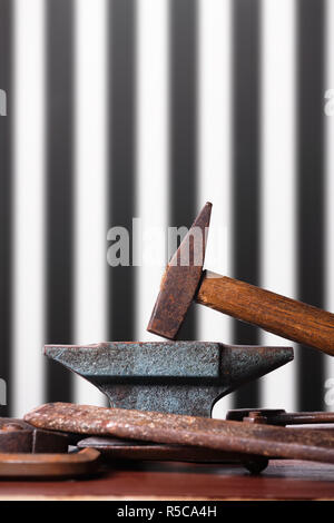 Old rusty rugged anvil, hammer and other blacksmith tools on striped black and white background. - Stock Photo