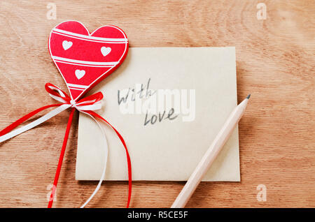 Card with Message With Love in the Letter and Wooden Red Heart on a Wooden table at Valentine Day. View from above - Stock Photo