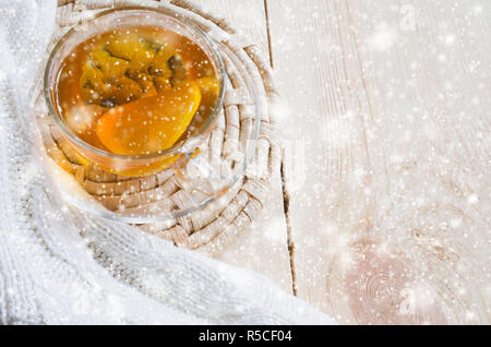Cozy and soft winter background. Cup of tea with lemon and warm knitted sweater or blanket on a vintage wooden board. Holidays at home. Snow Falling E - Stock Photo