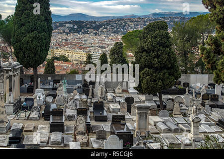 Graves and Tombstones on castle cemetery (cimetiere du chateau) in Nice France with the town in background - Stock Photo