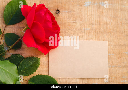 Red rose and empty greeting card. Holiday background. Flat lay style, top view. - Stock Photo