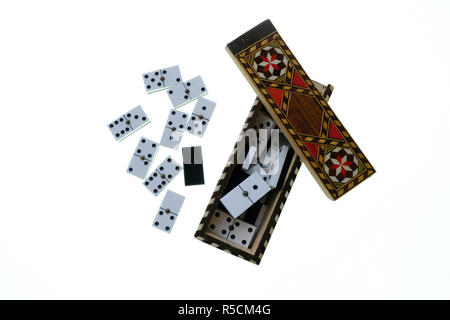 Small wooden marquetry box with sliding lid containing a set of small white dominoes with black dots. All against a white background - Stock Photo