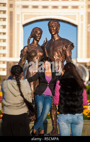 Kazakhstan, Astana, KazMunaiGas building home to the Oil and Gas Ministry, Two women taking photo of their friend posing by statue - Stock Photo