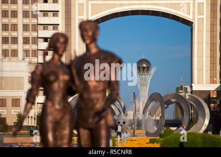 Kazakhstan, Astana, Statue infront of KazMunaiGas building home to the Oil and Gas Ministry, with Bayterek Tower in background - Stock Photo