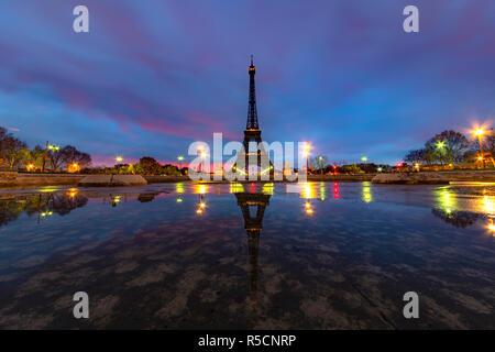Sunrise on the Eiffel tower reflection on the Trocadero fountain water in Paris, one of the most visited building by the tourists - Stock Photo