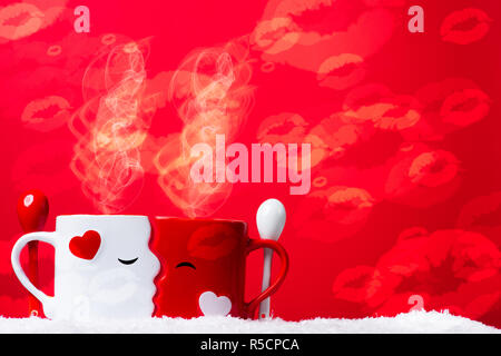 Love at coffe time, valentine's concept, two mugs forming a couple of lovers kissing each other against a red backdrop on a snow bed. - Stock Photo