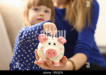 Child little girl arm putting coins into piggybank Stock Photo