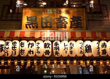 Lanterns and sign over restaurant in Shinjuku, Tokyo, Japan - Stock Photo