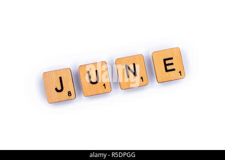 London, UK - July 8th 2018: JUNE, spelt with wooden letter tiles over a plain white background. - Stock Photo