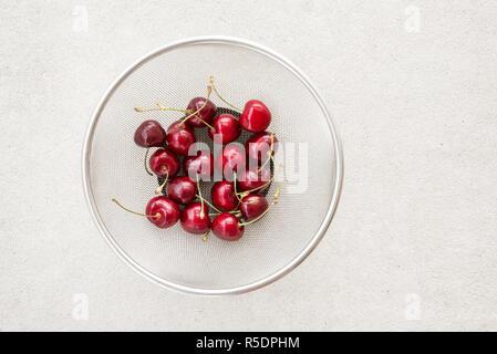 Fresh cherries in a round metal colander, on concrete background. - Stock Photo