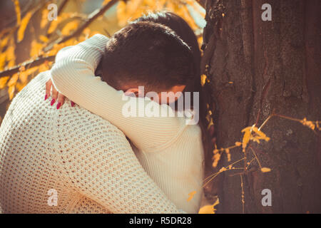 Careless couple standing next to beautiful tree and hugging each other - Stock Photo