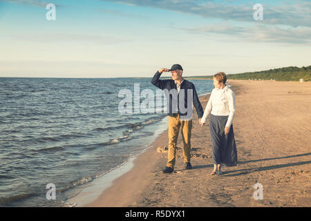 elderly couple having romantic walk on the beach at sunset - Stock Photo