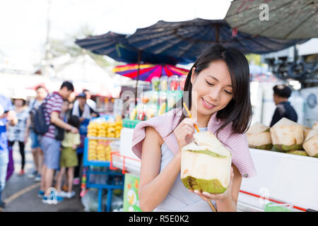 Woman enjoy coconut juicy in street market - Stock Photo