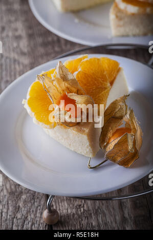 Cheesecake decorated with oranges and physalis - Stock Photo