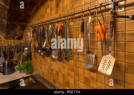 Kitchen utensils hanging on the wall of a vintage kitchen. - Stock Photo