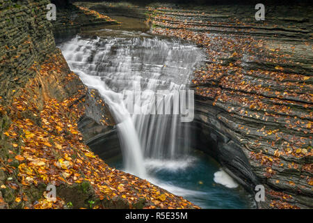 The first drop in a series of waterfalls called The Triple Cascade splashes through a rocky gorge decorated with colorful fallen autumn leaves at Watk - Stock Photo