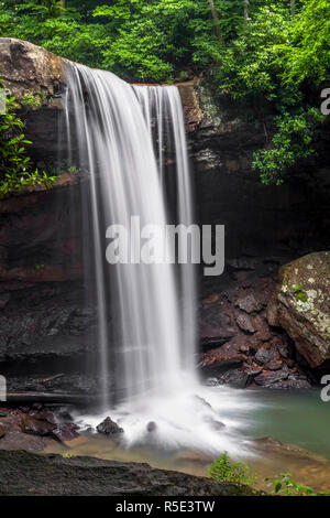 Cucumber Falls, a beautiful waterfall in Pennsylvania's Ohiopyle State Park, plunges over an overhanging woodland cliff. - Stock Photo