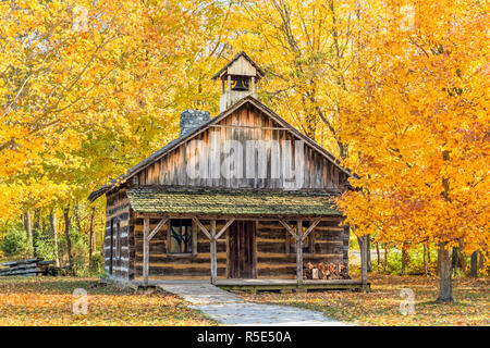 A log church is surrounded by colorful autumn trees in an Indiana park. - Stock Photo