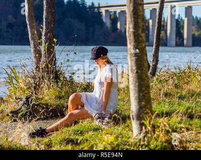 Adolescent teenager girl pretty natural in nature sitting near lake dressed in short White robe dress - Stock Photo