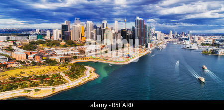 New modern urban developmen Barangaroo on shores of Sydney Harbour in Sydney city CBD under cloudy sky in aerial panorama over waters of Darling harbo - Stock Photo