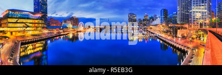 Dark blue hour in Sydney over Darling harbour Cockle bay on Sydney harbour between modern urban buildings and high-rise business towers with bright il - Stock Photo