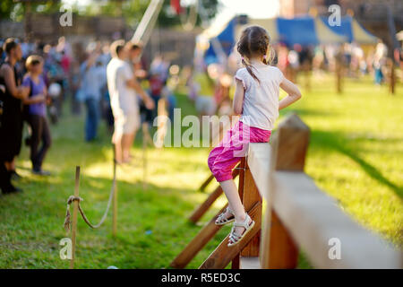 Children having fun during annual Medieval Festival, held in Trakai Peninsular Castle. Recreating medieval town spirit. - Stock Photo