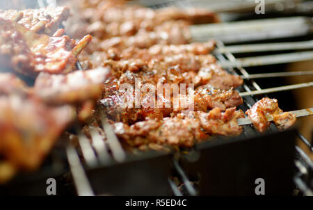 Chicken kabobs grilled on metal skewers outdoors - Stock Photo