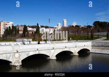 Cyclist crossing Puente del Rey bridge over Manzanares River in Virgen del Puerto Gardens, Madrid, Spain - Stock Photo
