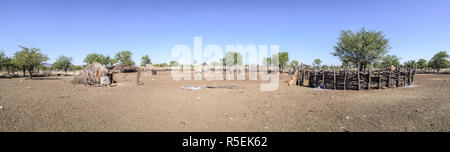 Panoramic view of a Himba village showing the main hut, the sacred fire and the corral. - Stock Photo