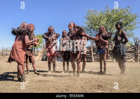 Group of Himba women with traditional dresses dancing in a circle, some of them while carrying their babies on their backs. - Stock Photo