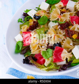 mediterranean farfalle with dry tomatoes and pine cores - Stock Photo