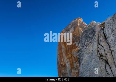 Iron tinted eroded granite rock against blue sky - Stock Photo