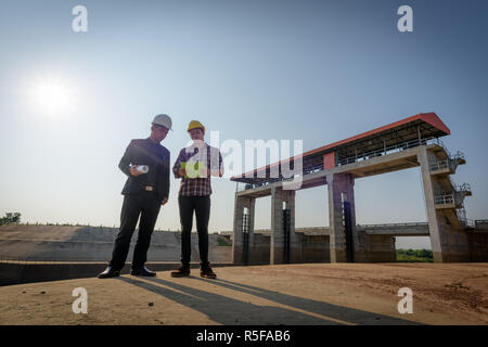 Business men meeting with Engineers and foremen are standing reading reports on construction sites. - Stock Photo
