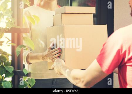 woman accepting a home delivery of boxes from delivery service courier - Stock Photo