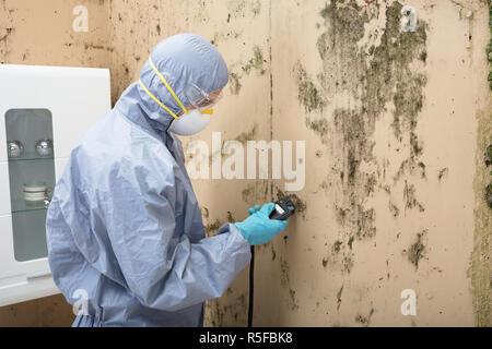 Technician Installing TV Satellite Dish On Wall - Stock Photo