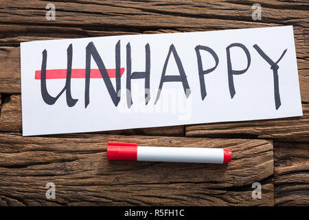 Unhappy Word On Paper With Strike Out Un Text - Stock Photo