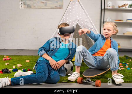 boy using virtual reality headset  and his sister pointing by finger while sitting on skateboard near wigwam at home - Stock Photo